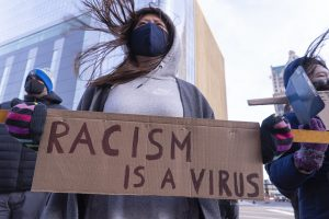"""protest featuring sign that reads """"Racism is a virus"""""""