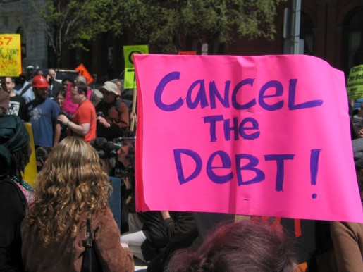 """Photograph of a crowd in the street for a political demonstration. A large pink sign in the foreground says """"Cancel the Debt!"""""""