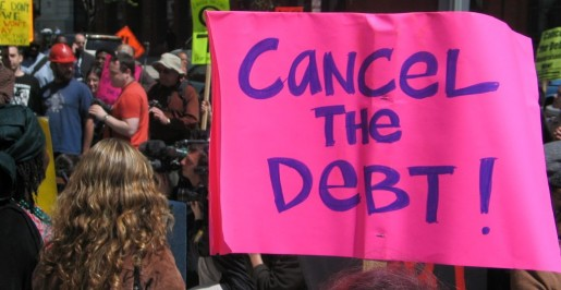 "Photograph of a crowd in the street for a political demonstration. A large pink sign in the foreground says ""Cancel the Debt!"""
