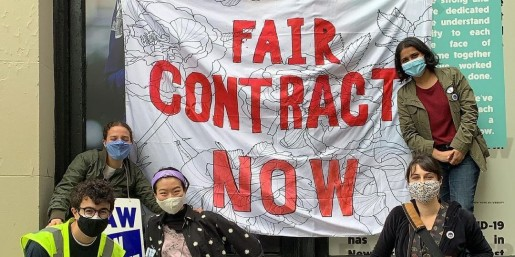 "Banner that reads ""Fair Contract Now"" hung on a building with a group of graduate students on the picket surrounding it"